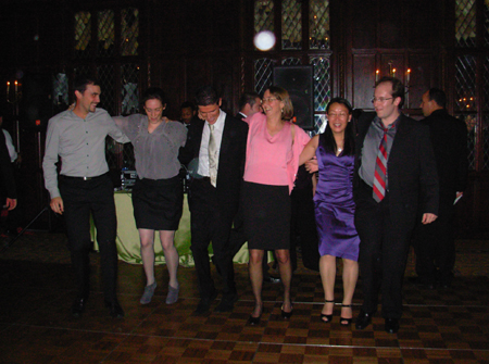 Lab members dance in a line while wearing suits and dresses.
