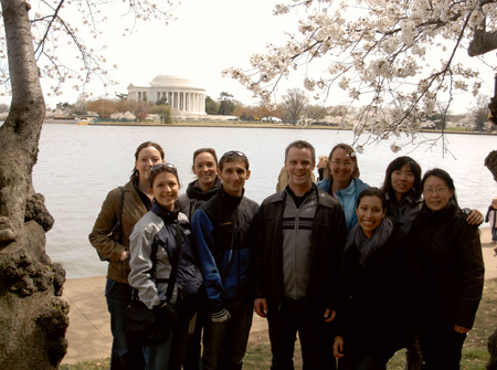 Lab members stand under cherry blossoms in front of the Tidal Basin in Washington DC. The Jefferson Memorial is in the background.