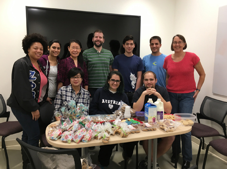 Lab members gather around a table with bags and containers of cookies.