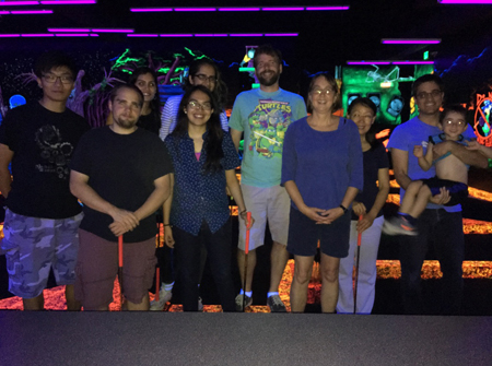 Lab members pose at an indoor mini-golf course lit with neon lights and blacklights.