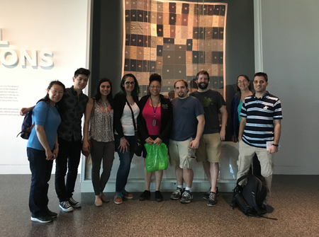 Lab members gather in front of a mounted tapestry in the African American History Museum.