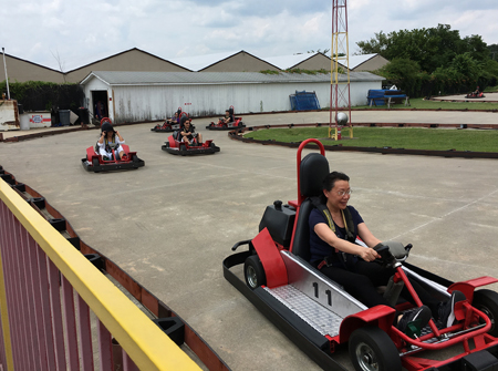 Lab members driving red and black go karts around a track.