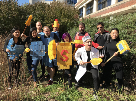 Lab members pose outside wearing 'armor' and wielding 'weapons' made of pipette tip racks.