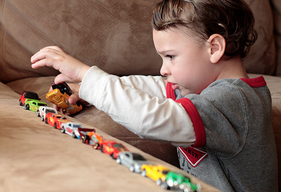 Stock image of a boy playing with toy cars