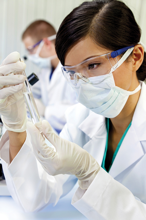 Researcher wearing safety goggles, surgical mask, and latex gloves, examining the contents of a test tube.