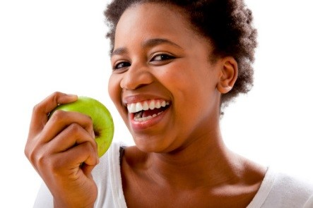 Woman smiling as she prepares to eat an apple.