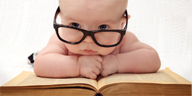 baby in glasses on top of book