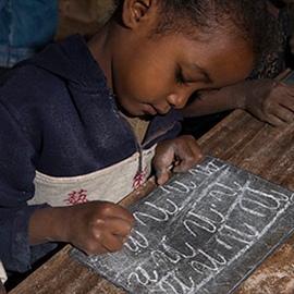 small child writing on small chalkboard