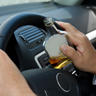 Hands holding car steering wheel while clutching liquor bottle.
