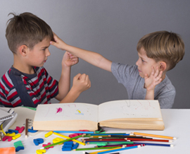 Two young boys showing signs of aggression towards each other.