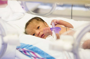 Preterm infant in hospital bed