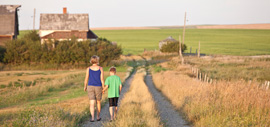 A mother and son walking down a rural road.