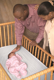 Two parents standing over a crib, with their child sleeping on its back