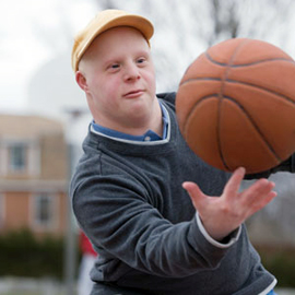 Boy with Down Syndrome playing basketball