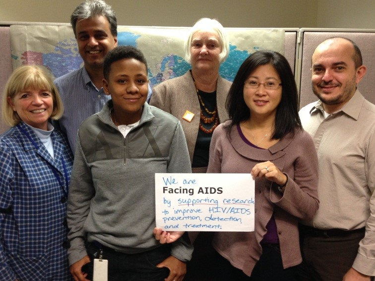 Dr. Rohan Hazra (back row, far left) poses with other NICHD researchers who focus on HIV/AIDS for the #FacingAIDS campaign. Their sign reads: We are #FacingAIDS by supporting research to improve HIV/AIDS prevention, detection, and treatment.