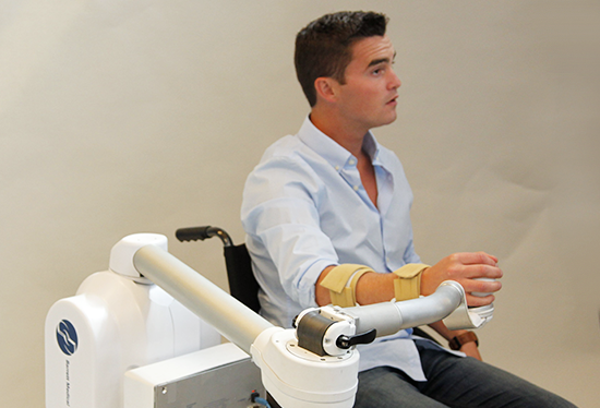 A man uses a robotic arm for  rehabilitation therapy. Credit: William Townsend, Barrett Technology