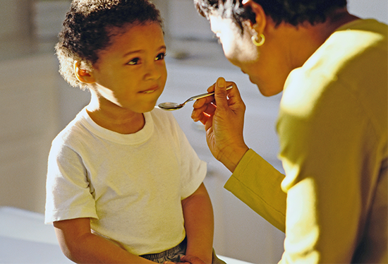 Stock image of child receiving medicine.