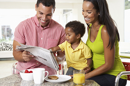 Parents and toddler reading newspaper