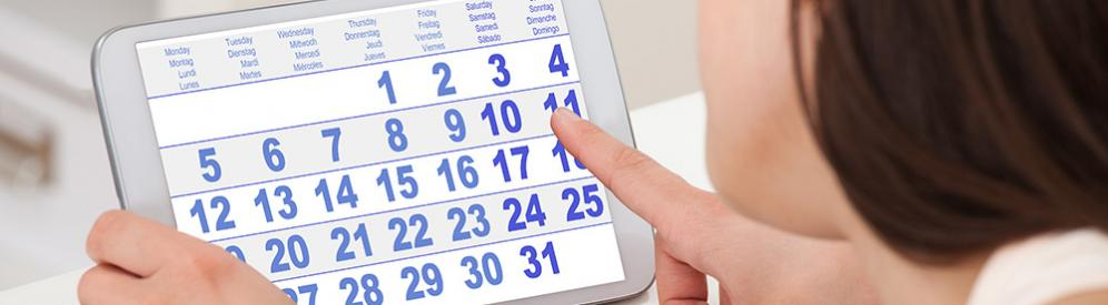 A woman counting days on a monthly calendar on a tablet computer.