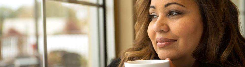 A woman smiling and holding a coffee mug while looking out a window.